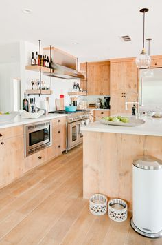 Bright kitchen with reclaimed beetle wood cabinents, glass pendant lights, and white cabinents