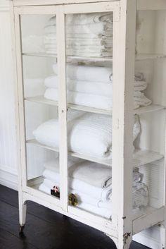 Vintage medicine cabinet as linen storage.