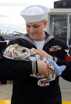 A USS Norfolk sailor holds his newborn son. | 48 Soldiers Meeting Their Children For The First Time