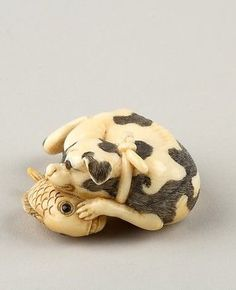 Netsuke of a Dog and a Fish, Ivory, horn, Japan.