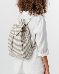 """A simple canvas satchel for daily essentials. Roomy, but still neatly sized. Dimensions: Measures 10.5"""" x 15"""" x 5"""". Details: 100% 16 oz. recycled cotton canvas. Drawstring and flap closure with metal"""