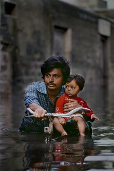 A father carries his son through the monsoon waters in Porbandar, Gujarat.