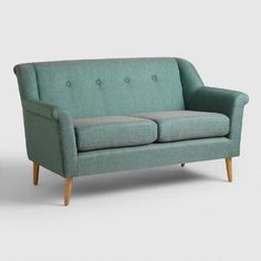 Covered in two-tone teal fabric with hints of gray, this compact sofa brings mid-century style to your living area with a wing-arm silhouette, Danish-inspired tapered legs, clean tailored lines and button tufting. This classic love seat features reversible seat cushions that extend the life of your piece with a simple flip.