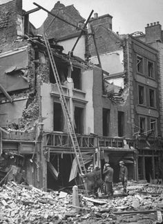 1940, Rescue workers using ladder to check for survivors amid the destruction wrought by German bombs during regular German air attacks against the city.