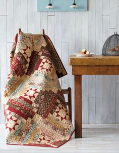 "Marianne combined two of her favorite traditional blocks in this throw– Log Cabin and Variable Star. She chose one red print for the stars to make them stand out on the scrappy background. This fat quarter friendly quilt is featured on Fons & Porter's ""Love of Quilting"" 2500 TV series."