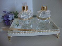 Kit contém:  - bandeja de MDF pintada, espelhos na parte interna e decorada em meia pérola. Pés egípcios.  - frasco de vidro porta sabonete líquido decorado em meia pérola, strass dourado e laço pingente. Capacidade de 250 ml.  - frasco de vidro para difusor de varetas decorado em meia pérola, st...