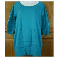 """80s Style Wide Neck Long Teal Sweatshirt Worn once at most. Good condition. No tears, holes or stains.   3/4 sleeve long sweatshirt with kangaroo front pocket. Boat neck, can be worn off 1 shoulder. Sequin stripe down each arm. (All intact)  60% Cotton - 40% Polyester  Juniors X-Large = Women's Medium/Lrg  Approx measurements:  - 19"""" armpit to armpit - 26 1/2"""" length  Let me know if you have any questions. Check out the rest of my items to bundle with & save on shipping. Tops Sweatshirts…"""