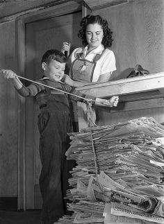 United States February, 1942.A patriotic boy who is doing his part for the home front war effort, ties a rope around a pile of newspaper for recycling.