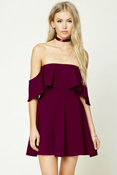 A stretch knit mini dress featuring an off-the-shoulder silhouette, a flounce top layer, short flounce sleeves, and a flared skirt.