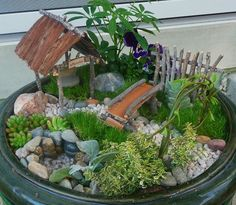 Bridge over rocky waters -Inspiration for new life for an old pot/container. This is so charming.