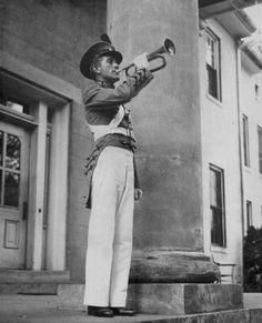 Bugler, Kentucky Military Institute, Lyndon, Kentucky. Angled view of a man in white pants and dark jacket blowing a bugle on the porch of a building, beside a column. The school was founded in 1845 by Colonel Robert Thomas Pitcairn Allen. It closed in the early 1971 and was consolidated into Kentucky Country Day School.