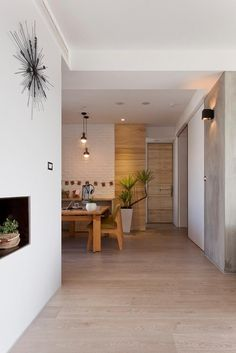 Wood cladding has also been taken up and over the walls to bring more warmth into the minimally decorated apartment, and much of the furnitu...