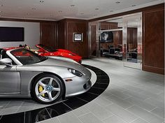 The modern gentleman's lounge featuring a custom auto showroom with car turntable. #mancaves #cars #luxury #DreamHome