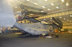 Marines from VMM-165 work on their V-22 Osprey in the hangar bay of USS America on July 16, 2016, during RIMPAC. Though the aircraft was folded up for this maintenance job, the ship has high hat spaces that can fit a V-22 with its wings out and nacelles up when needed. USNI News photo.