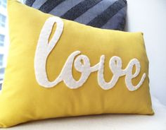 Yellow Love PIllow. $42.00, via Etsy. I'm sure you can do it cheaper though :-) and maybe in an aqua or cream (my bed linen colours)