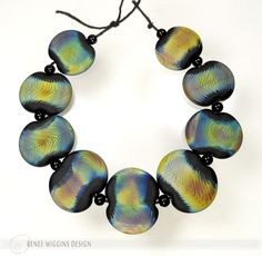 "Renee Wiggins Design ~ ""Solar Winds"". Flattened tab hand crafted lampworked glass beads made with a beautiful reactive glass in a twisted cane technique over opaque black, etched matte for a velvety surface texture. 6/2016"