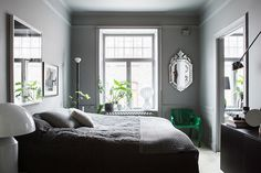 Dark grey and green in the bedroom of the home of Swedish interior designer Lotta Agaton.