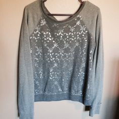 Gray Hollister Sweater Hollister long sleeve sweater that has lighter gray sleeves and a darker gray middle area. The front has a silvery flower pattern that shines a bit. •Reasonable offers considered! •No trades! •No PayPal! •Pet Free! •Smoke Free! Hollister Sweaters Crew & Scoop Necks