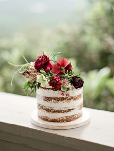 Thinly iced cake with red, plum & foliage | Photograph: Danielle M. Sabol // Florals: Everly Alaine Florals // Cake: Green Lily Bakery // via Magnolia Rouge