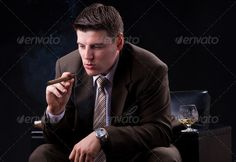 Businessman sitting on a couch with an drink and a cigar  ...  Smoker, addiction, adult, attractive, background, beauty, black, brandy, business, businessman, cigar, cigarette, cognac, confident, dark, drink, elegant, enjoyment, expression, face, fashion, fumes, glass, habit, hand, handsome, hat, human, lifestyle, male, man, men, old, one, people, person, portrait, relaxation, smoke, style, suit, tobacco, vintage, whiskey, white, young