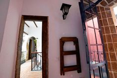 Unique experience in Seville/ Sevilla (Spain). Beautiful DIY/ handmade rustic wood ladder for hanging bunk beds in a rustic bedroom with distressed stone brick wall and black metal street lamp for lightning. DIY handmade rustic barn/ sliding door. DIY red brick flooring. Rustic home with distressed stone brick walls in Southern Spain. Ideas, design and more info on juancarloscoquerel.com
