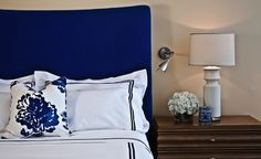 Gorgeous cobalt blue headboard paired with black and white hotel bedding and a bold cobalt blue floral pillow. A wooden nightstand is topped with a tall ceramic table lamp, flowers and blue and white box. Tan colored wall feature a small brushed nickel adjustable reading sconce.