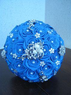 Buquê Azul Royal c/ 5 Broches (Pérolas e Strass) <br>Lindo Buquê produzido com rosas super delicadas em Cetim no tom de Azul Royal. <br> <br>Detalhes do Buquê: <br>* Composto por 5 Broches; <br>*Pérolas em Todos os Miolos das Rosas. <br>* Florzinhas de strass, espalhadas pelo Buquê. <br>* Fita Rendada na base do buquê <br>* Fitas de cetim envolvendo a haste <br>* Laço de cetim, com uma delicada fita no Cabo. <br>* Strass no Cabo. <br> <br>Os Buquês são personalizados conforme a sua escolha…
