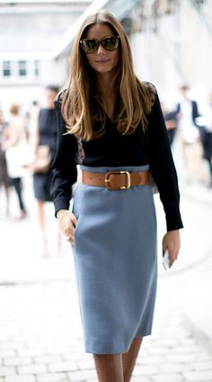 Black blouse with light blue skirt with large leather belt.