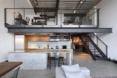 Cuisine bois et gris et escalier en métal menant vers le deuxième étage