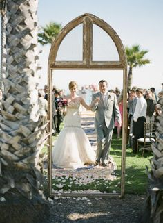 the rustic door in the middle of the outdoor ceremony, and second, the mats and petals that ply the role of an isle runner. Stunning!
