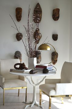 Beautiful vignette with cream and brass upholstered chairs, white lacquered sculptural table, and a gallery wall of african masks | Tompkins Lloyd Interiors
