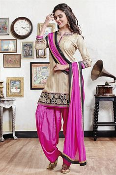 Beige & pink color cotton fabric suit. High neck suit is now in trend, fancy buttons are enhanced across neckline and edge of the kameez is engraved with sequins and zari work in floral pattern. Color combination used to design this piece is amazing and team matching color accessory with this suit. This suit is accompanied with matching Patiala and dupatta.