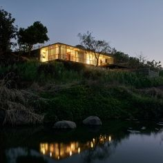 Riverside+house+by+Architecture+Brio+is+partially+embedded+in+a+grassy+hillock