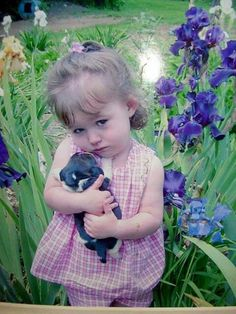 A little girl and her puppy in the iris garden.