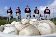 Baseballs sit in a bucket as Minnesota Twins pitchers run a drill during a baseball spring training workout Monday, Feb. 27, 2012, in Fort Myers, Fla. (AP Photo/David Goldman)