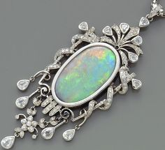 An opal and diamond pendant with chain   centering one large oval-shaped opal cabochon, measuring approximately 33.00 x 19.00 x 6.00mm.; estimated total diamond weight: 4.90 carats; mounted in fourteen karat white gold; length: 18½in.