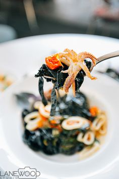 Lanewood Studio Food Photography. This dish can be found at Ray's and Stark Bar in Los Angeles. The house made pasta called Bucatini is made with squid ink pasta, sungold tomatoes, mint, opal basil, Calabrian chile, calamari, collator, and bottarga. Shot for Locale Magazine.