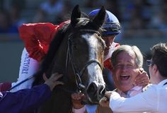Lanfranco Dettori, left, hugs trainer Sir Michael R. Stoute as he celebrates atop Queen's Trust after she nosed out Lady Eli in another thrilling distaff stretch duel in the Breeders' Cup, this time in the Filly & Mare Turf. The day after Beholder and Songbird.