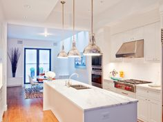 Open kitchen with three nickle pendant lights and marble counters in a LEED certified townhouse