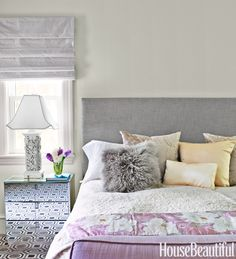 In the master bedroom, antique chinoiserie lamps are a nice contrast to the straight, simple lines of a headboard upholstered in a Designers Guild linen.