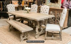 Rustic meets refined - handcrafted reclaimed wood table with beautiful scrolled trestle legs and cream linen dining chairs, sold as a six piece. www.designaclickaway.com