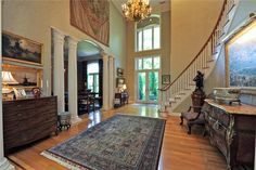 ENTRANCE- EIGHT FOOT GLASS PANED DOUBLE DOORS W/TRANSOM, TWO STORY CEILINGS, HARDWOOD FLOORS W/ DECORATIVE BOARDER INLAY, CROWN MOLDING, HANGING CHANDELIER W/ CEILING MEDALLION AND MOTORIZED LIFT, WINDING STAIR CASE W/ ARCHED CAT WALK,COAT CLOSET