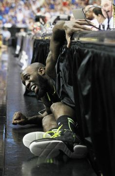 Baylor's Quincy Acy comes out from under the tables on press row after a play against Kentucky during the second half of an NCAA tournament South Regional finals college basketball game Sunday, March 25, 2012, in Atlanta. (AP Photo/John Bazemore)