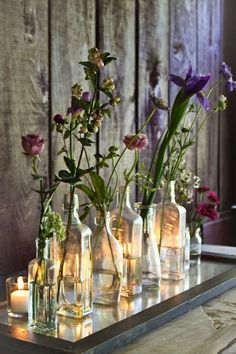 this floral arrangement in vintage bottles with tea-light candles behind, would also look good with white flowers Tea Light Candles, Tea Lights, Candle Lighting, Deco Floral, Vintage Bottles, Antique Bottles, Bottles And Jars, Small Bottles, Apothecary Bottles