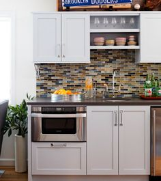 Contemporary basement featuring a kitchenette with eye-catching backsplash