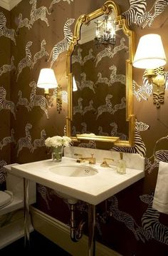 Powder Bath by Melissa Warner Rothblum - marble sink, Scalamandre's zebra wallpaper and Alexa Hampton's Ginger sconces - with a pretty gold mirror. Tres chic!