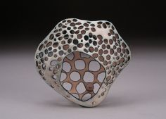 Danielle Embry........Connie Fox:  Use of holes of different sizes unifies the front and back.
