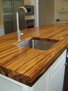 Wide-plank hardwood countertops add natural beauty. Each plank runs the length of the countertop, and the surface can be stained in a variety of colors. Photo courtesy of Brooks Custom.
