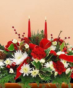 This stunning #ChristmasCenterpiece contains red carnations and hypericums along with white cushion pom poms and white statice. Noble fir and white pine tips add the perfect holiday touch along with red velvet ribbon and ornamental gold b