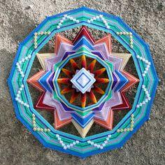 Coloris chatoyants et enroulements successifs du fil autour de bâtons, composent avec harmonie ce Mandala.
